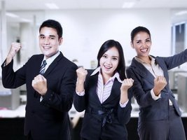 Successful business people celebrating a triumph with arms up at the office